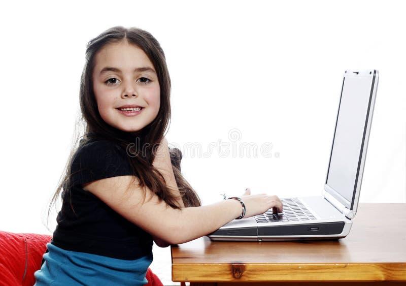 Meisje dat aan laptop werkt stock foto's