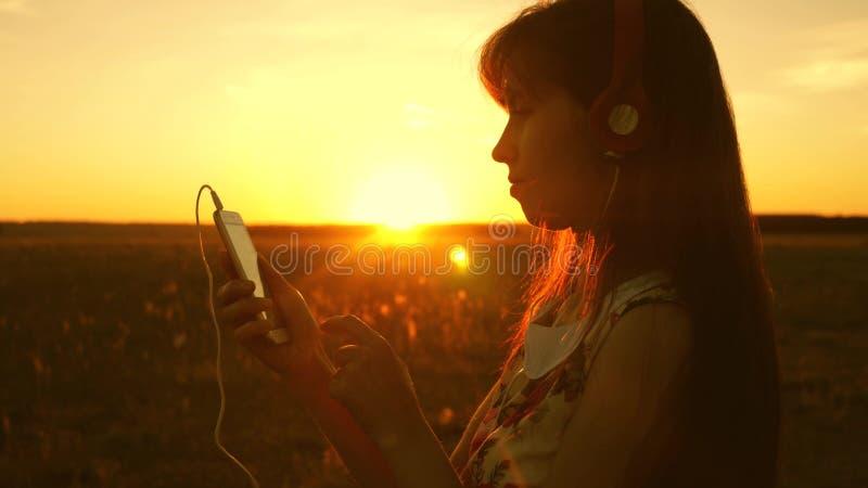 Meisje dat aan muziek luistert en in de stralen van een mooie zonsondergang danst een jong meisje in hoofdtelefoons en met een sm stock afbeelding