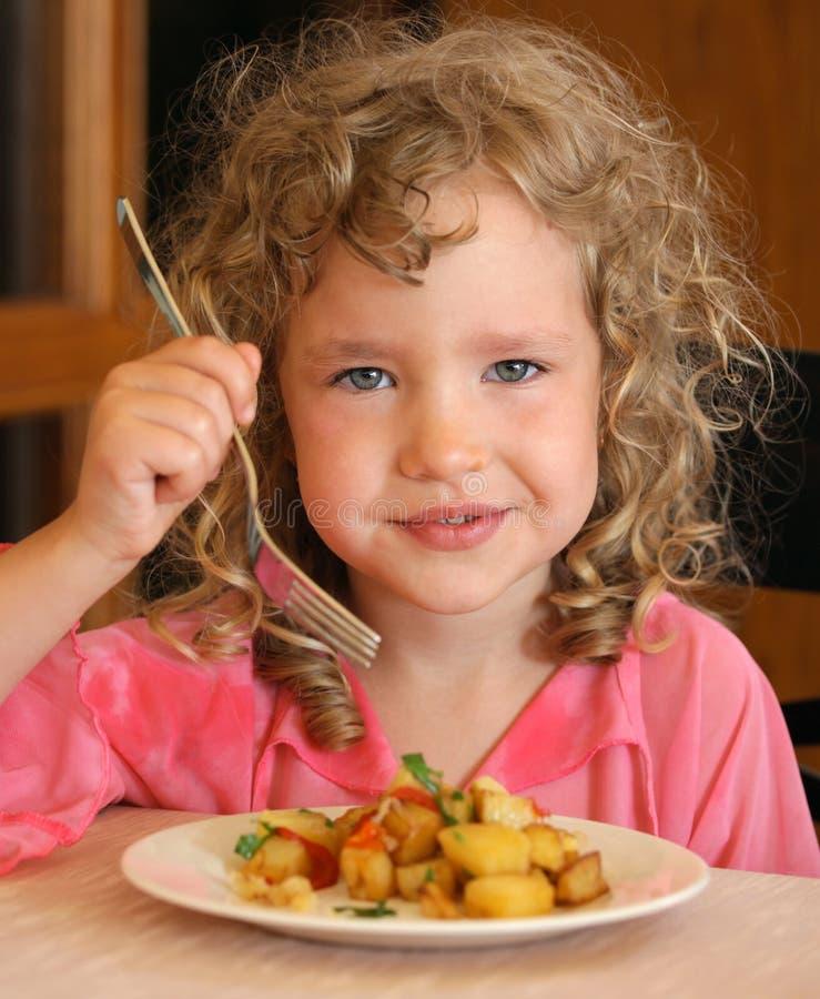 Meisje dat aardappels eet royalty-vrije stock afbeelding