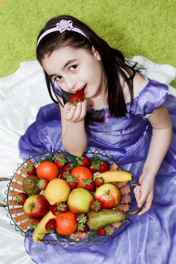 Meisje dat aardbei eet stock foto's