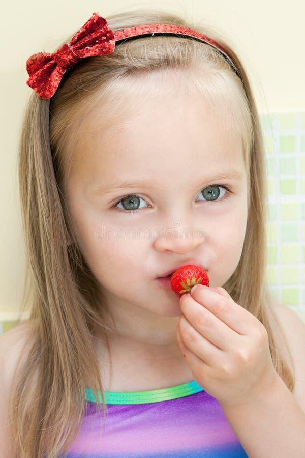 Meisje dat aardbei eet royalty-vrije stock afbeelding