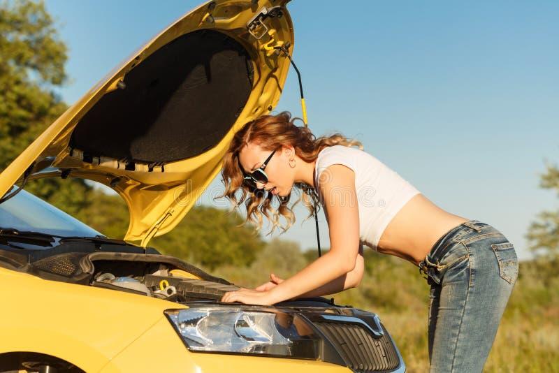 Meisje dat auto herstelt stock fotografie