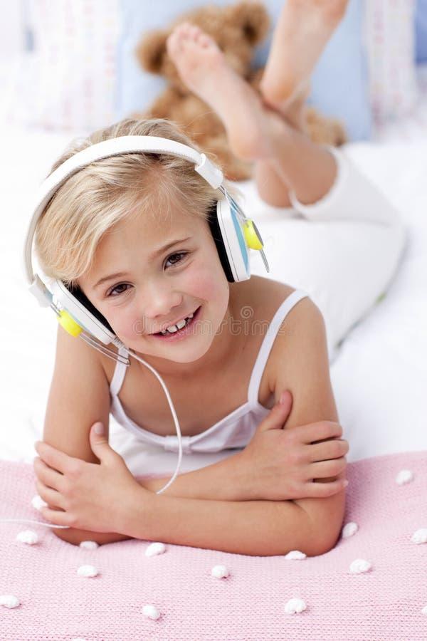 Meisje dat in bed ligt dat aan de muziek luistert royalty-vrije stock fotografie