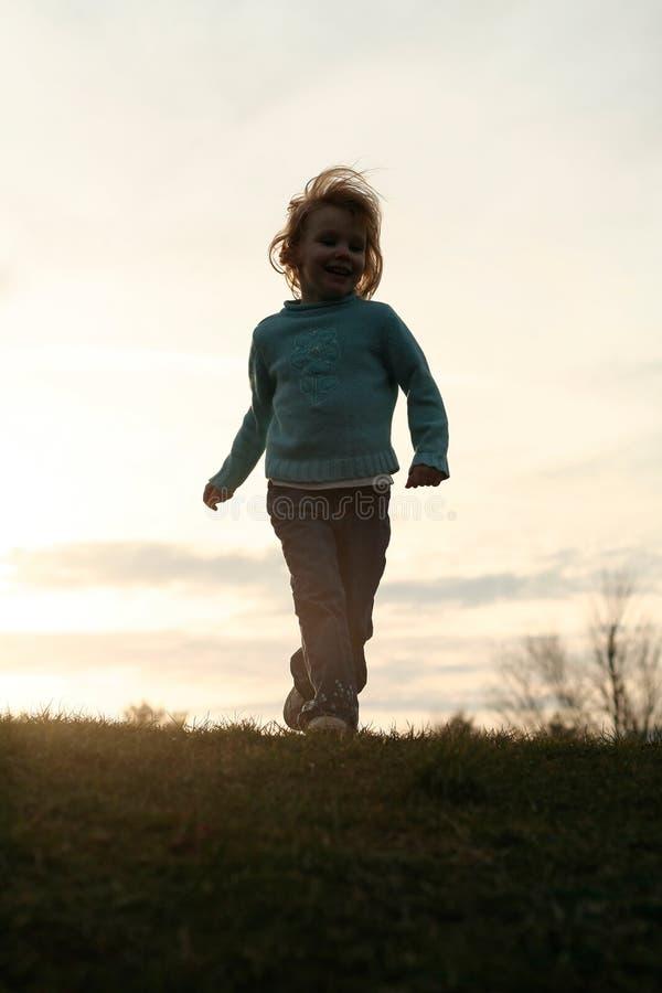 Meisje dat bij zonsondergang loopt stock afbeelding