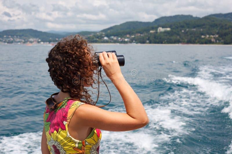 Meisje dat in binoculaire overzeese kust waarneemt stock afbeeldingen
