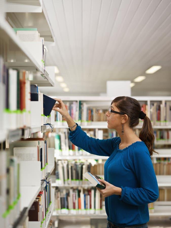 Meisje dat boek in bibliotheek kiest royalty-vrije stock foto