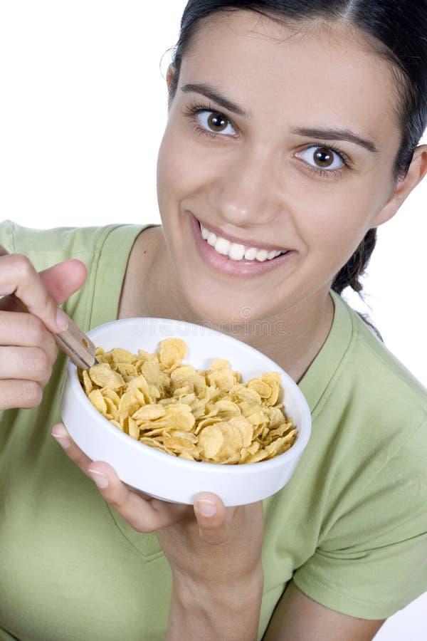 Meisje dat cornflakes eet stock foto's