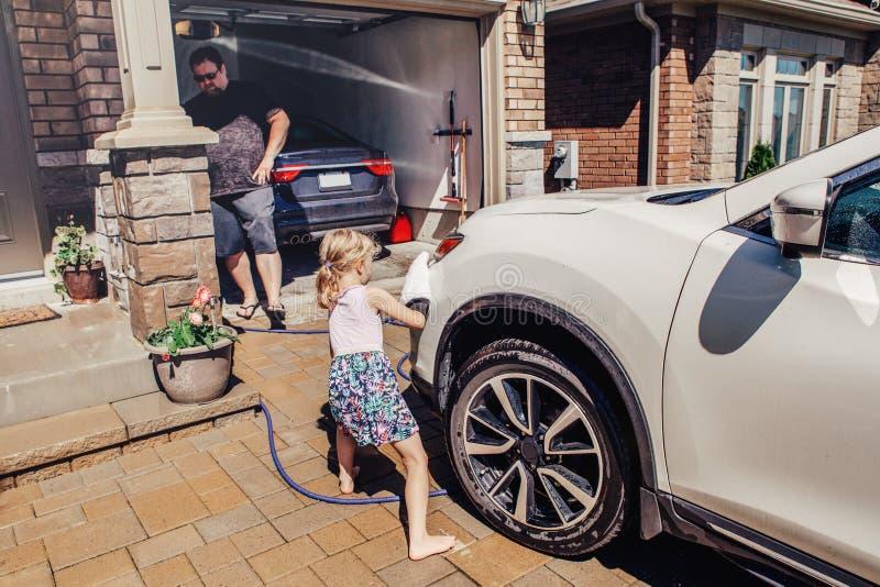 meisje dat de auto van de vaderwas op oprijlaan vooraan huis op de zomerdag helpt royalty-vrije stock afbeeldingen