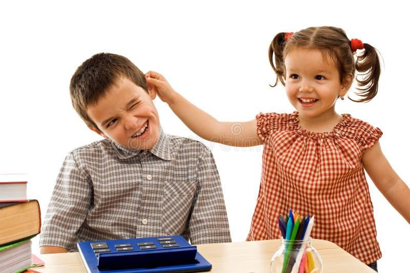 Meisje dat de jongen houdt door het oor royalty-vrije stock afbeeldingen