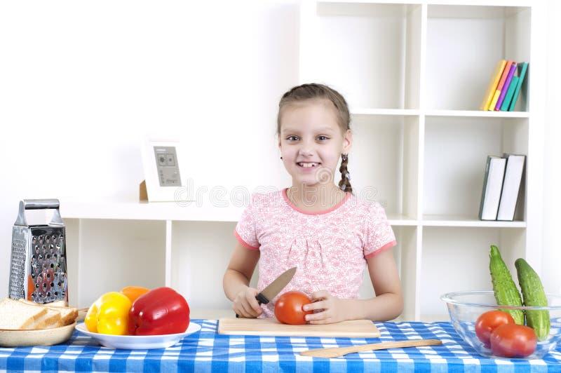 Meisje dat in de keuken scherpe groenten werkt stock foto's