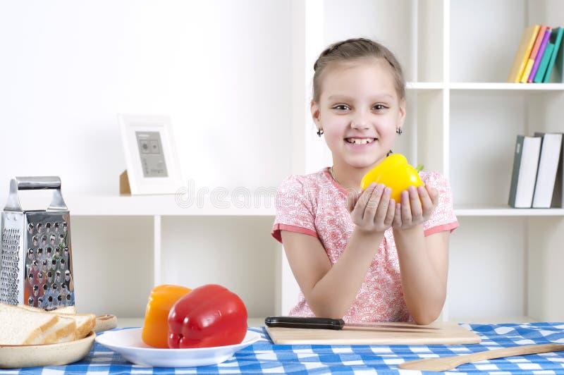 Meisje dat in de keuken scherpe groenten werkt stock fotografie