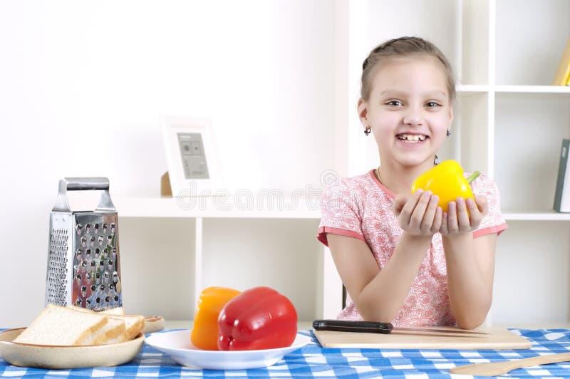 Meisje dat in de keuken scherpe groenten werkt stock afbeeldingen
