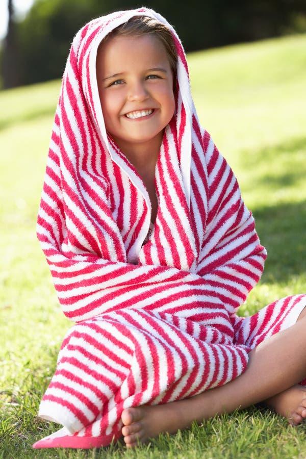 Meisje dat in de Zitting van de Handdoek in Tuin wordt verpakt stock afbeeldingen