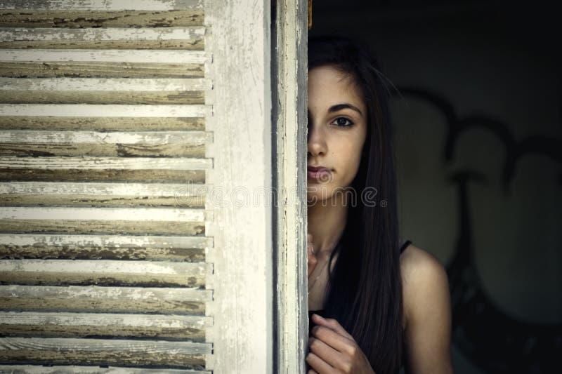 Meisje dat door een vensterblind kijkt royalty-vrije stock foto