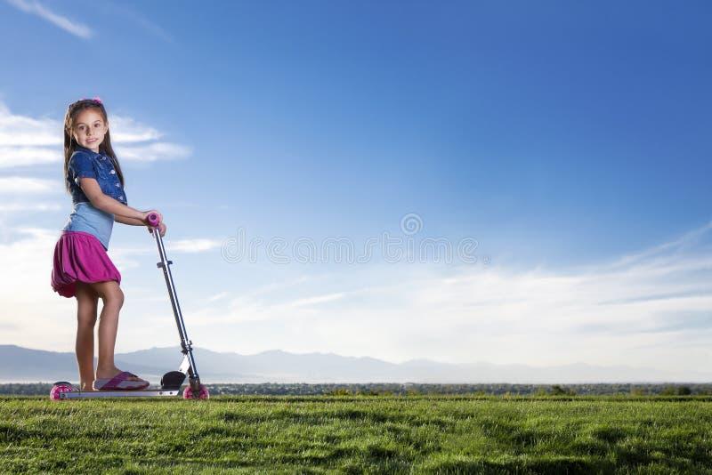 Meisje dat een autoped in openlucht berijdt stock afbeelding