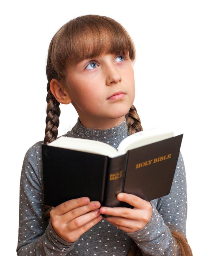 Meisje dat een Bijbel leest stock fotografie