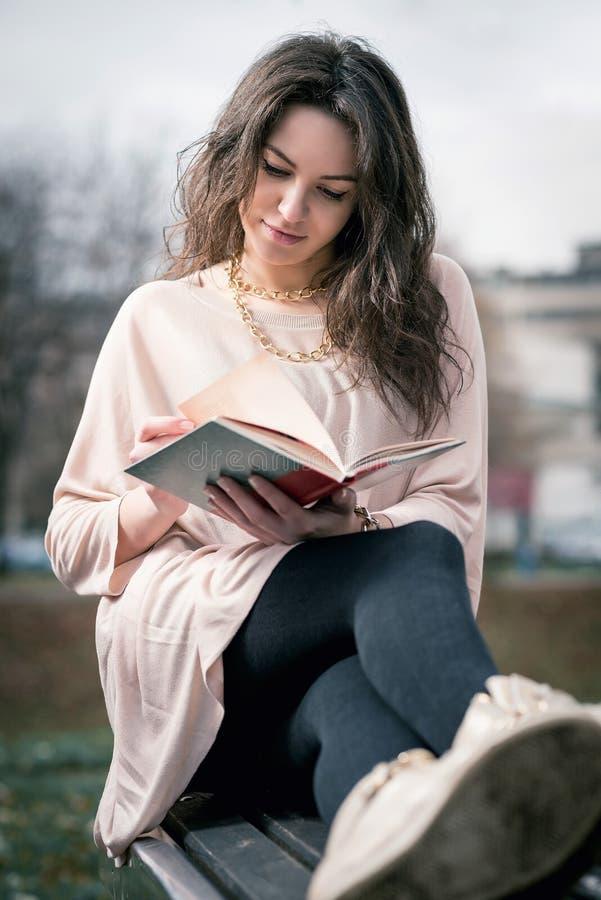 Meisje dat een boek in park leest stock foto's