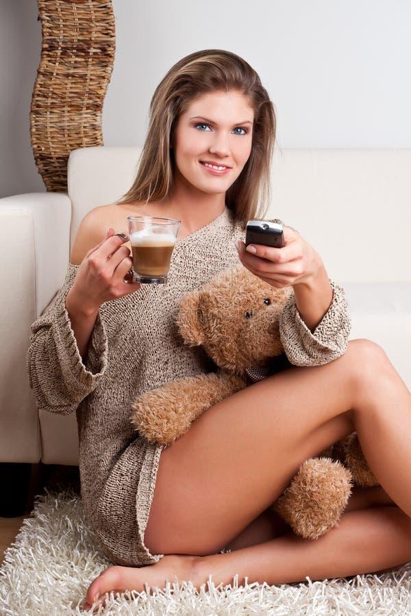 Meisje dat een kop van koffie en een afstandsbediening houdt stock afbeelding