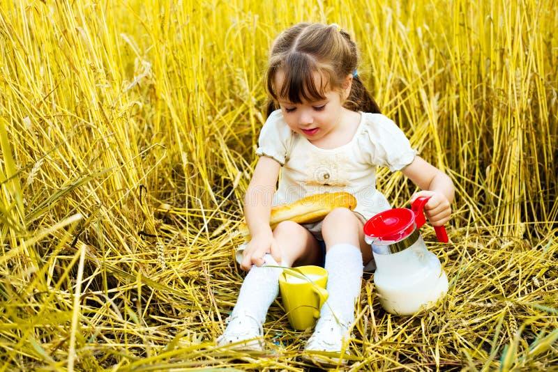 Meisje dat een lange brood en een melk eet stock afbeeldingen
