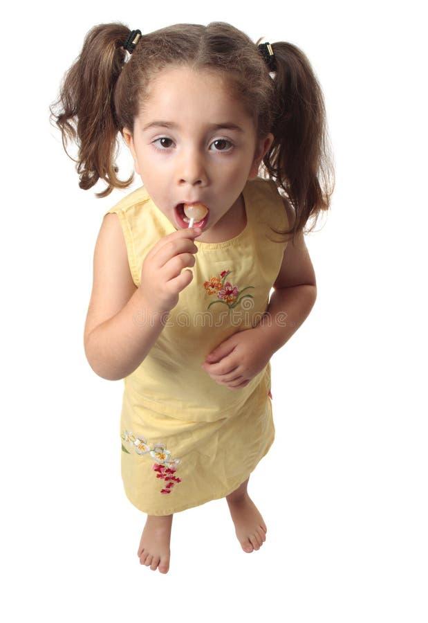 Meisje dat een lollysuikergoed eet royalty-vrije stock afbeelding