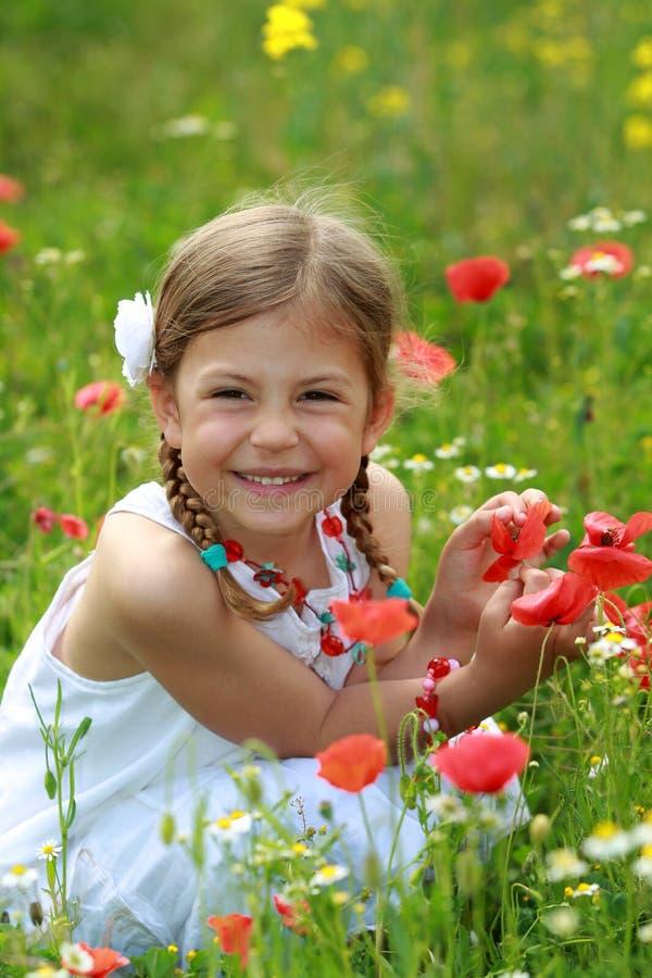 Meisje dat een rode papaver houdt stock foto