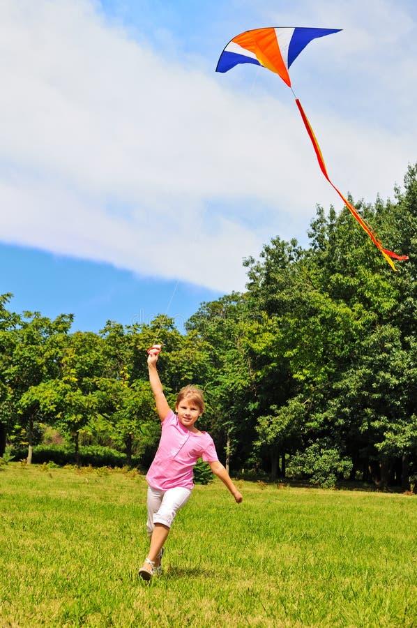 Meisje dat een vlieger vliegt stock afbeelding