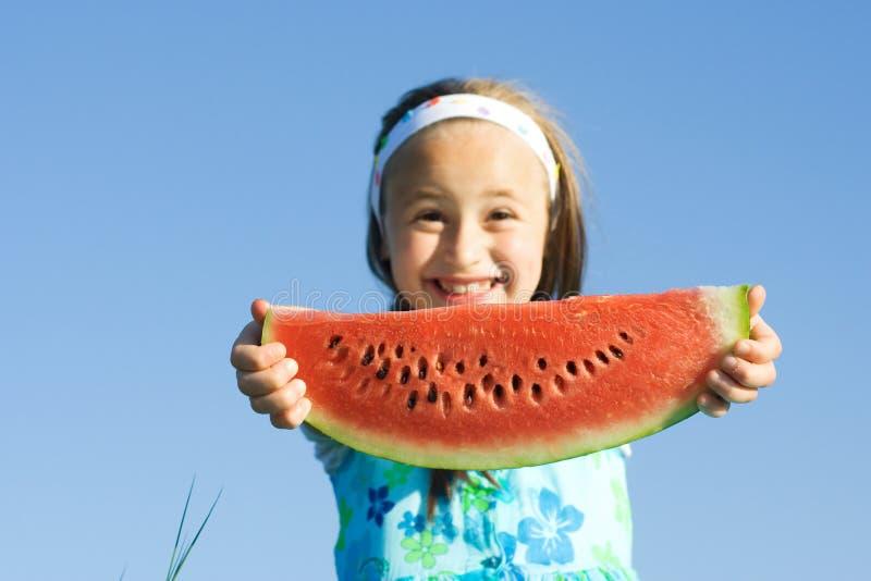 Meisje dat een watermeloenplak toont stock foto's