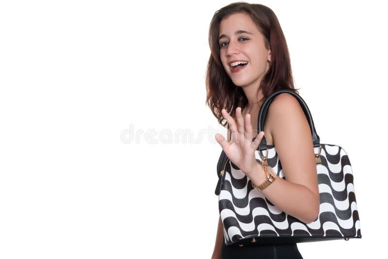 Meisje dat een zwarte en kleding en een beurs draagt die vaarwel glimlachen golven stock fotografie