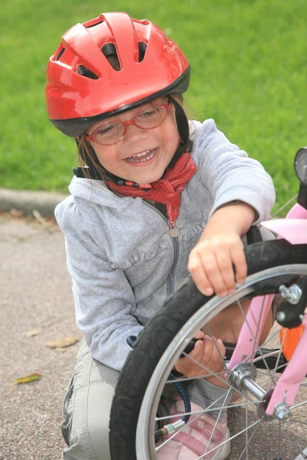 Meisje dat fiets herstelt stock afbeeldingen