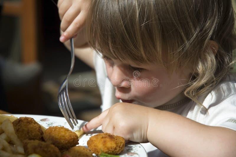 Meisje dat frieten eet stock afbeelding