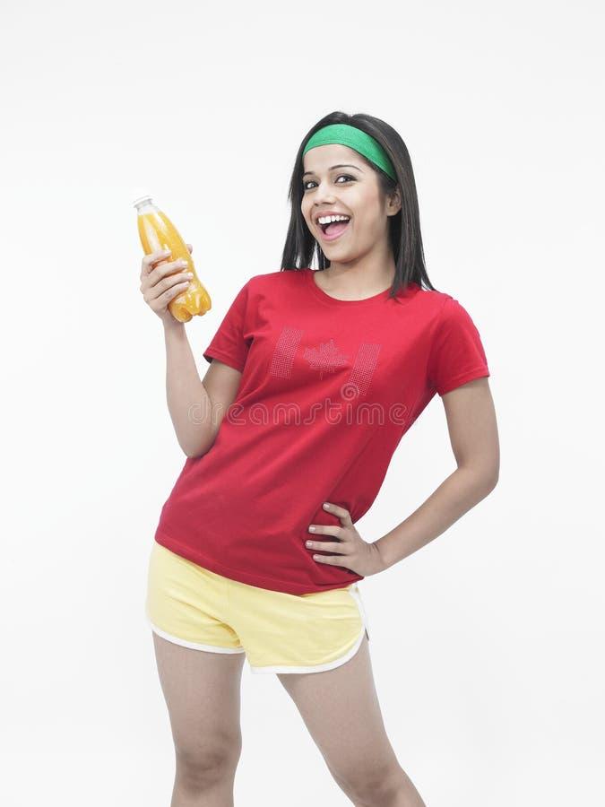 Meisje dat gebotteld jus d'orange drinkt stock foto