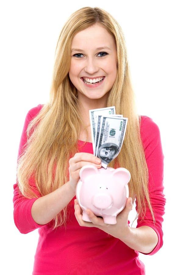 Meisje dat geld in spaarvarken zet stock fotografie
