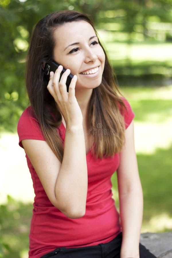 Meisje dat gelukkig op de telefoon babbelt stock afbeeldingen