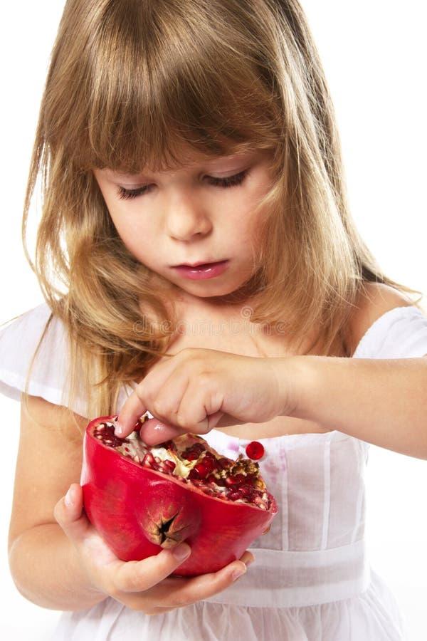 Meisje dat granaatappel eet stock foto
