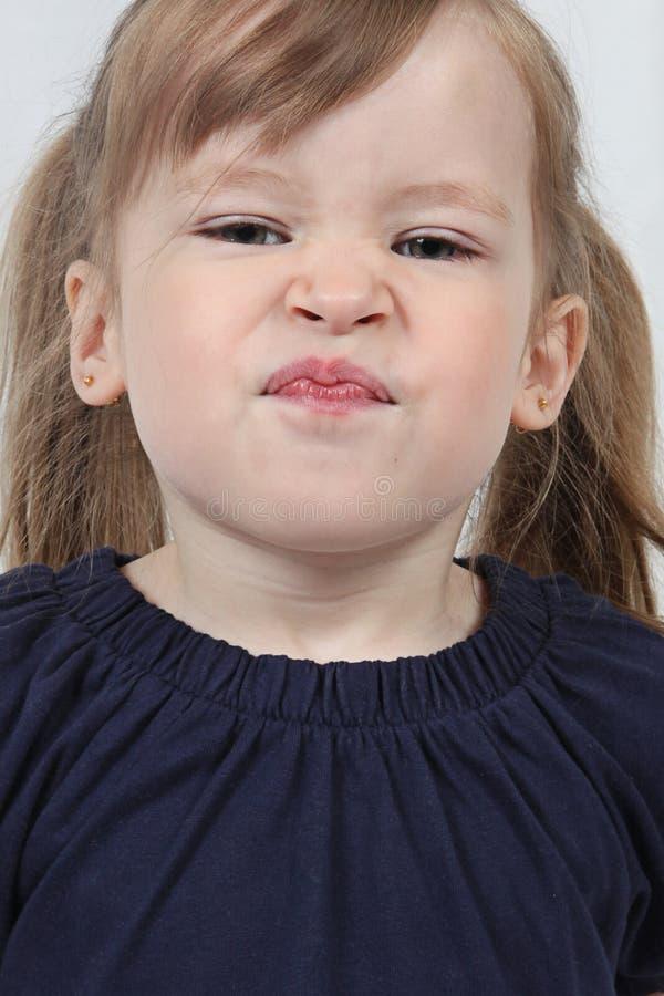 Meisje dat grappig gezicht trekt stock afbeelding