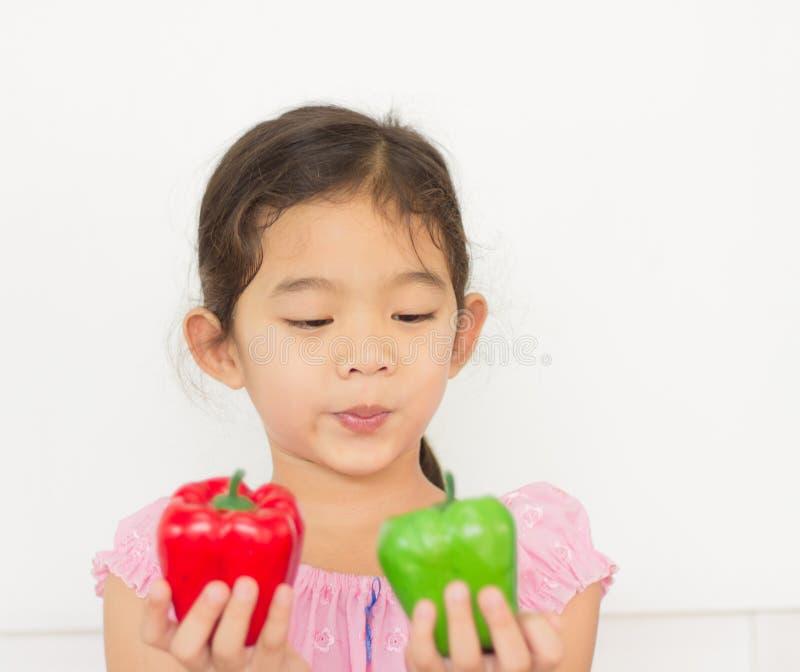 Meisje dat groene paprikafruit in haar hand kijkt stock afbeeldingen