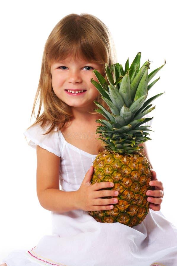 Meisje dat grote ananas houdt stock afbeelding