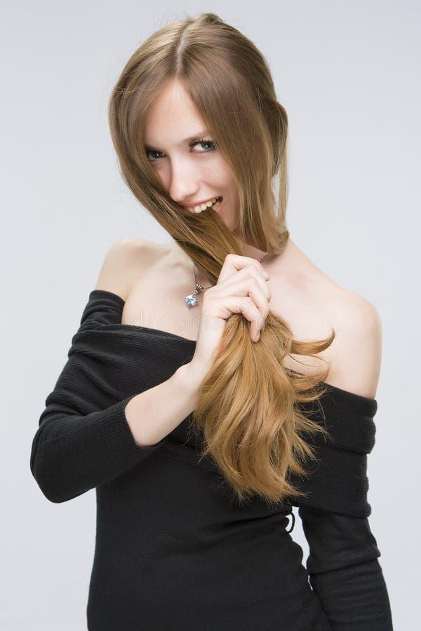 Meisje dat haar haar bijt stock afbeelding