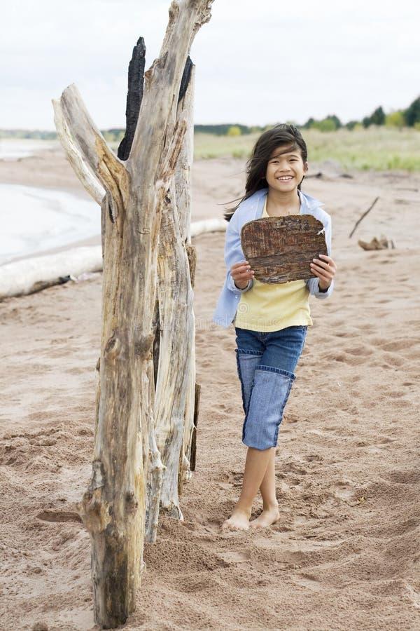 Meisje dat houten teken steunt stock foto