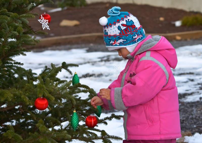 Meisje dat Kerstmisboom verfraait stock foto