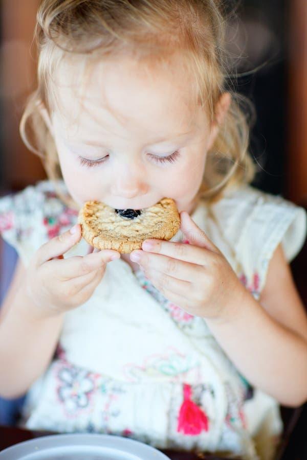 Meisje dat koekje eet stock afbeelding