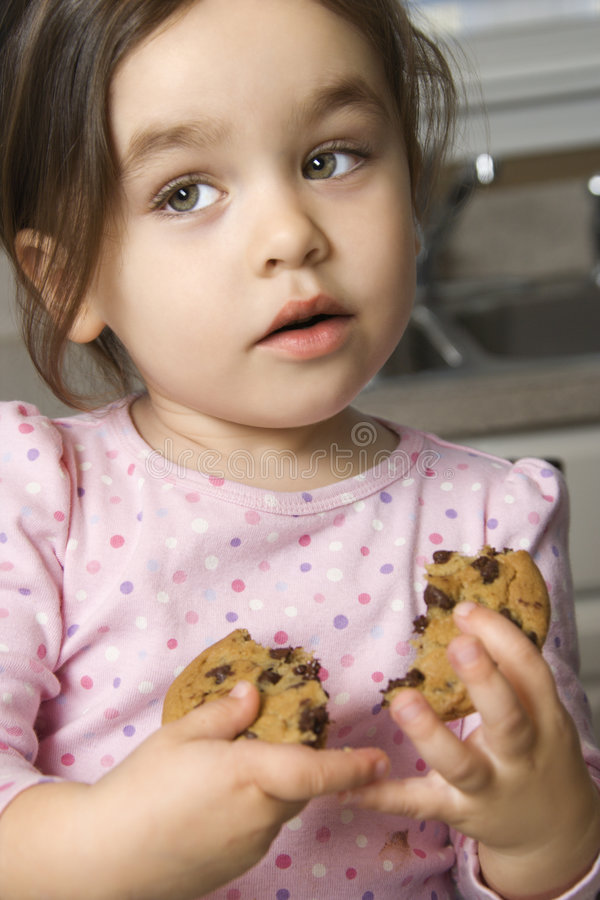 Meisje dat koekje eet. royalty-vrije stock afbeelding