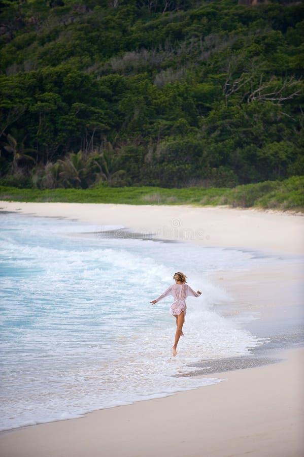Meisje dat langs de kust, Seychellen overslaat. stock foto's