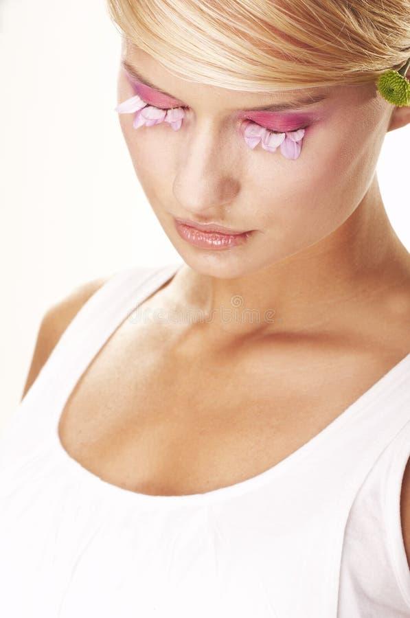 Meisje dat make-up draagt die van bloemen wordt gemaakt stock foto's