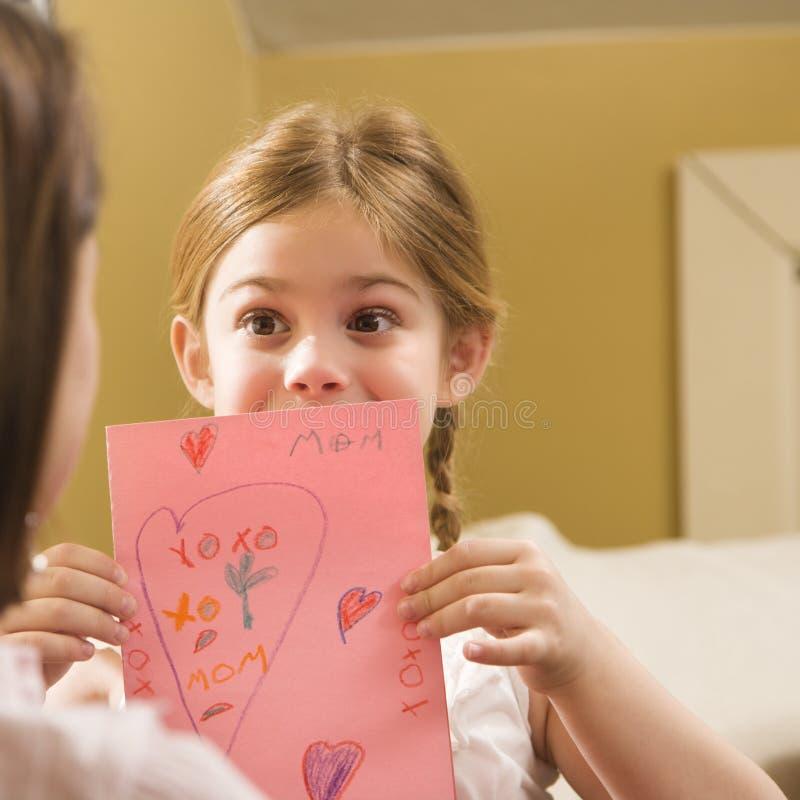 Meisje dat mamma een tekening geeft. stock afbeelding