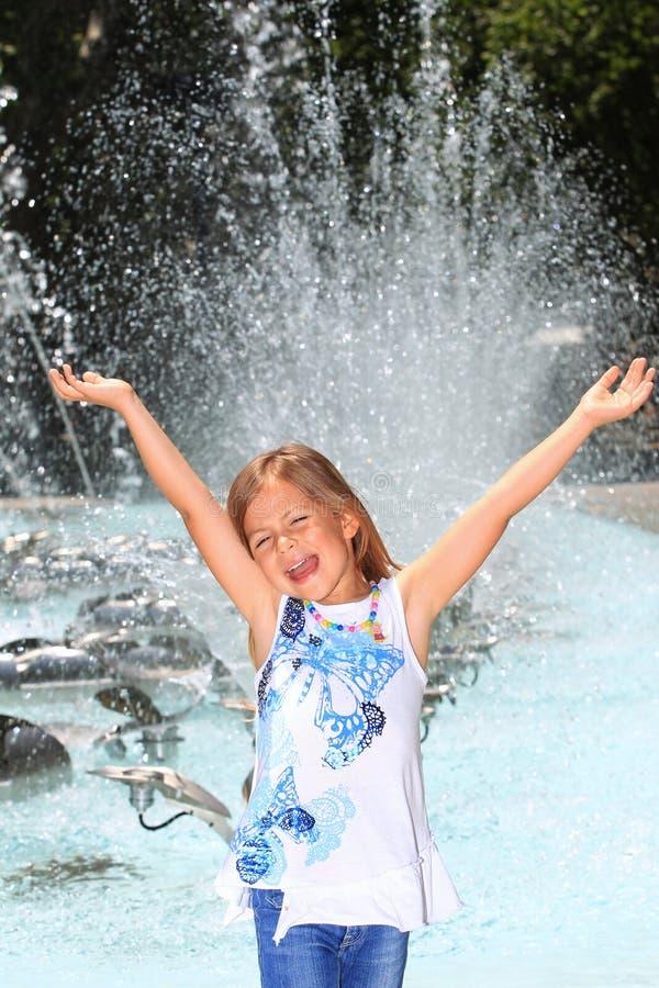 Meisje dat met verrukking door fontein gilt stock foto's