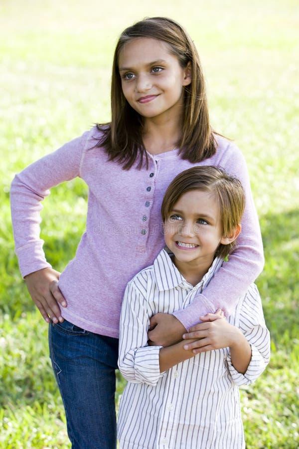 Meisje dat met weinig broer zich in openlucht bevindt stock afbeeldingen