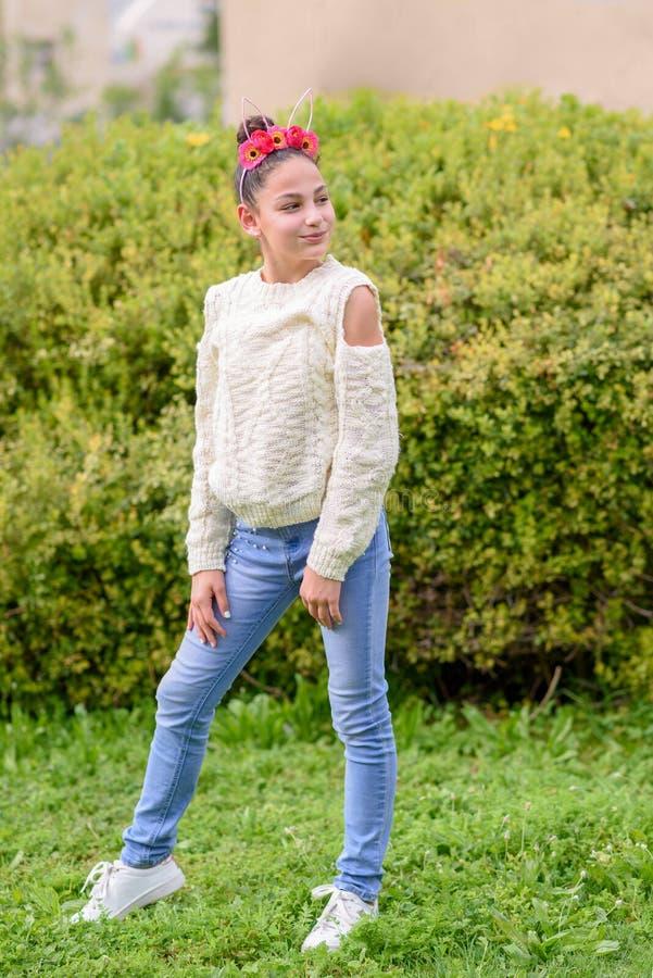 Meisje dat met zwarte kop een bloemenkroon draagt die voor aardachtergrond eenzich bevindt zonnige dag stock foto's