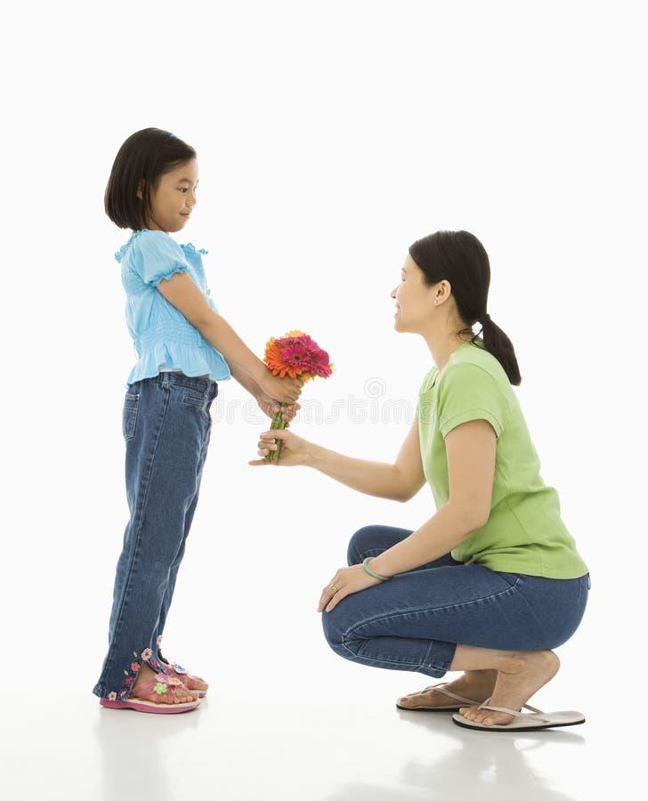 Meisje dat moederbloemen geeft. stock afbeeldingen
