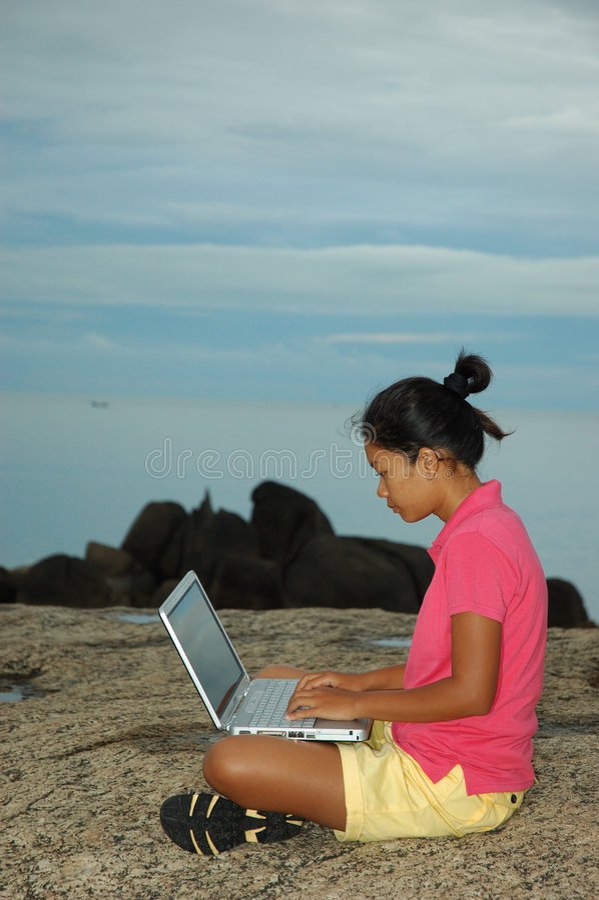 Meisje dat Notitieboekje buiten op Rotsen gebruikt stock foto